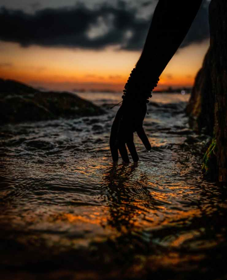 silhouette of person s hand touching water during sunset